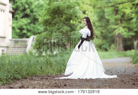 Woman in white Victorian dress in spring park