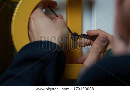 Intruder or Burglar with lockpick tool opens the front door to enter the house. could also be used for key service or locksmith concept