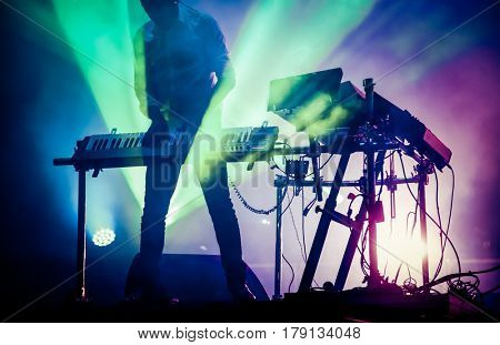 disc jokey mixing on stage over illuminated smoke background