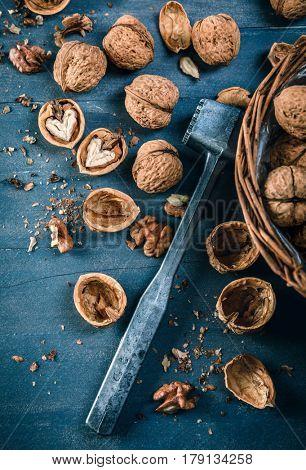 Walnut in wicker basket on blue old wooden board rustic style with nutshell top view.