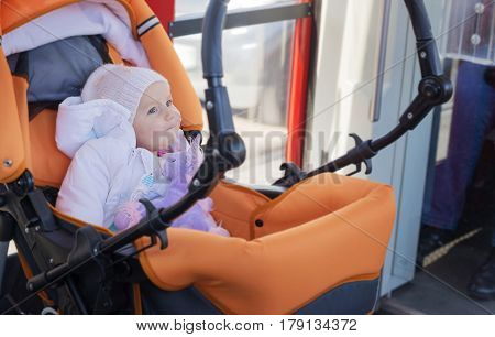 Little, darling, child goes by the tram in a carriage