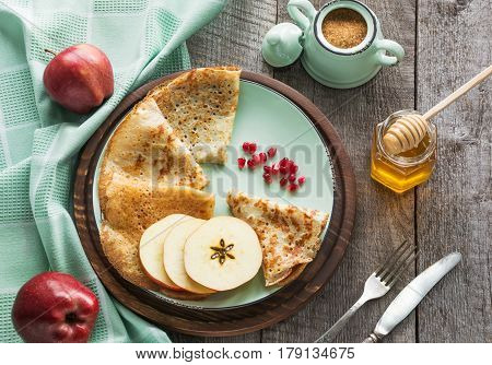 Tasty traditional russian breakfast of slapjack with honey on plate. Rustic style. Space for your text.
