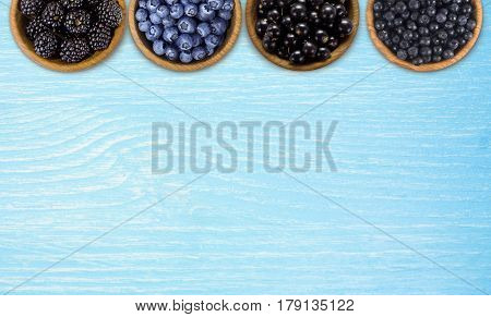 Black and blue berries. Blackberries blueberries currants and blueberries in a wooden bowls on a blue background. Berries at border of image with copy space for text. Top view.