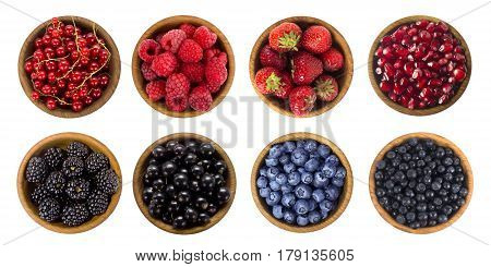 Black-blue and red berries isolated on white background. Collage of different fruits and berries. Blueberry blackberries cherry strawberry currant and raspberry. Collection of fruits and berries in a bowl. Top view.