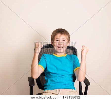 Happy teen boy in winning pose. Success kid in office chair happy ecstatic celebrating being a winner.