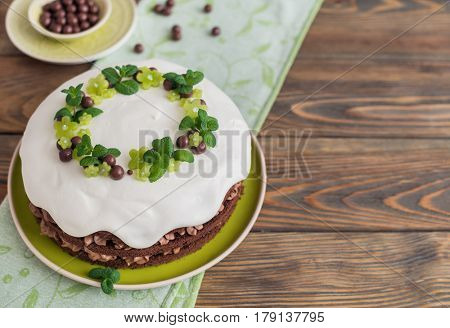 Homemade chocolate cake with cream on wooden background.