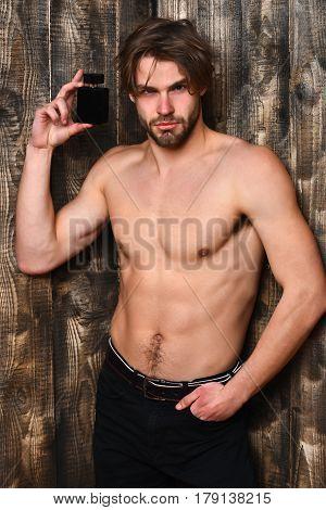 Caucasian Bearded Sexy Macho Man Holding Perfume