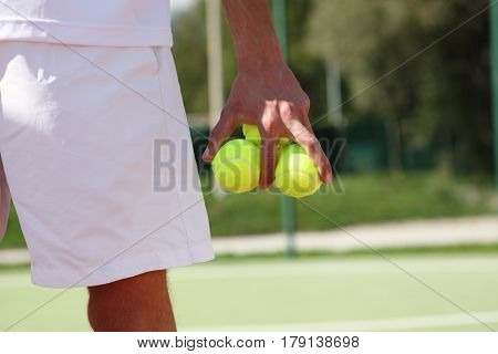 tennis player with balls in hand during a match game