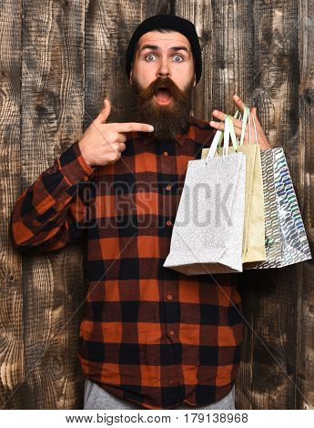 Bearded man long beard. Brutal caucasian surprised hipster with moustache holding shopping packages in red black checkered shirt on brown wooden vintage studio background