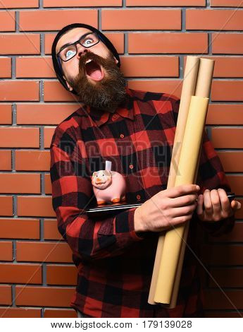 Bearded man long beard. Brutal caucasian shouting unshaven hipster holding craft paper rolls piggy bank on laptop in checkered shirt with hat and glasses on brown brick wall studio background