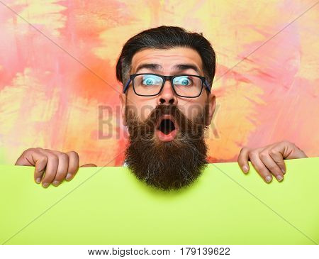 bearded man long beard brutal caucasian hipster with moustache on surprised face in glasses holding green paper on colorful background getting haircut by hairdresser at barbershop copy space