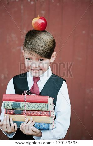 Portrait Of A First-grader Standing With Books And Apple On Head
