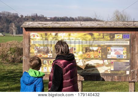 Ering,Germany-March 26,2017: A woman and her son look at a board with information about the Lower Inn European Nature Reserve