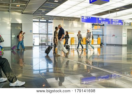 Frankfurt am Main Germany - October 11 2015: hurry people tourists with travel suitcase or bag luggage in airport or station terminal walks as blurred or defocused background in speed motion. traveling and business