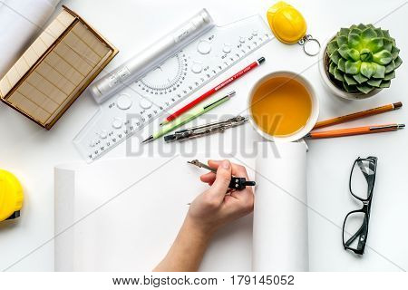 architect office with tools, hands, glasses and cup in profession concept on white desk background top view