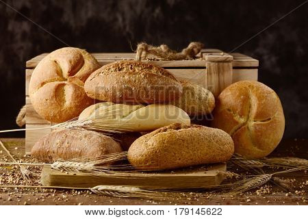 closeup of an assortment of different bread rolls and some wheat ears on a rustic wooden table