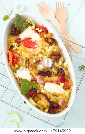 Pasta gratin with ham and vegetable in a white dish.