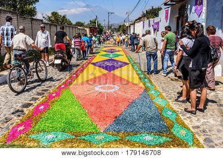 Antigua, Guatemala - March 26 2017: Locals admire street of dyed sawdust procession carpets during Lent in colonial town with most famous Holy Week celebrations in Latin America.