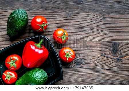 fresh vegetables in plastic tray from store on wooden desk background top view mock-up