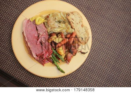 yellow dinner plate with Saint Patrick's dinner corned beef and cabbage,roasted potatoes and carrots,asparagus and Irish soda bread