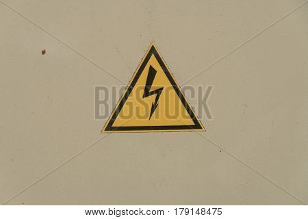 sign electrical hazard placed on the rusty metal panel.