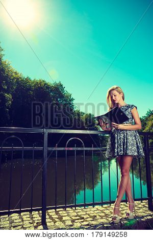 Technology outdoor relaxation concept. Woman in park relaxing and using tablet near river ebook spending her leisure time outside