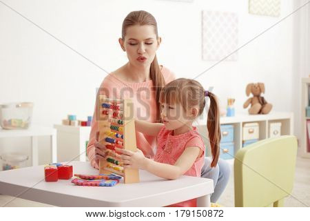 Cute little girl learning to count at private teacher's office