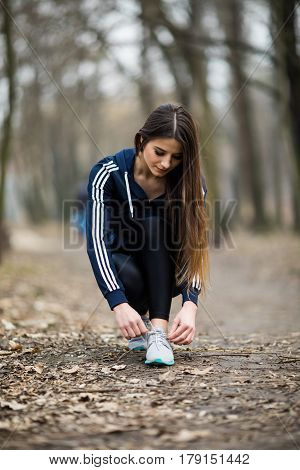 Sporty woman tying shoelace on running shoes before practice. Female athlete preparing for jogging outdoors. Runner getting ready for training. Sport active lifestyle concept. Close-up