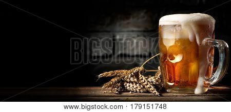 Beer in mug on wooden table near brick wall