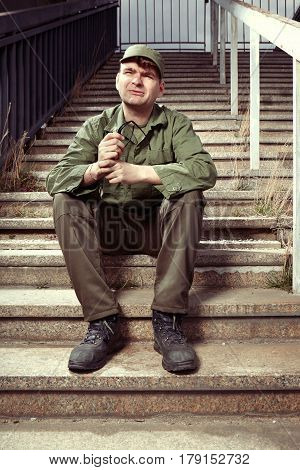 Soldier on sentry duty sitting in sunny city stairs