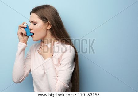 Young woman using asthma inhaler on color background