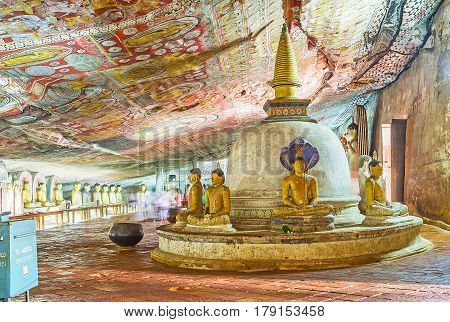 DAMBULLA SRI LANKA - NOVEMBER 27 2016: The old Stupa in Maharaja Lena Cave (Great Kings) of Dambulla Temple Complex surrounded by numerous painted statues on November 27 in Dambulla.