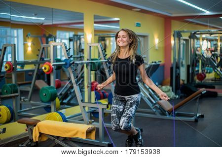athletic young woman in sportswear exercising with skipping rope at gym