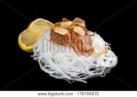 the cellophane with a piece of roasted salmon with tomatoes onion lemon and parsley isolated on black background