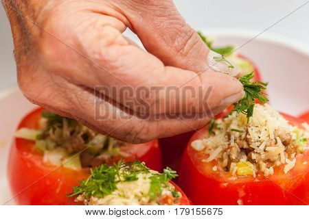 Stuffed tomatoes preparation : Adding coriander  to raw stuffed tomatoes