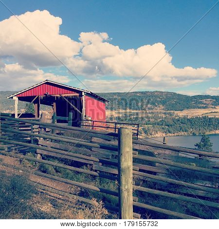 Red Barn On Hillside With Lake, Hills And Sky Background