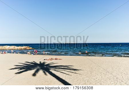 Santa Pola, Alicante Province, Spain - June 22, 2013: Sandy beach in fishery village of Santa Pola, with people relaxing and sunbathing in it. From the beach you can see the small Tabarca Island.
