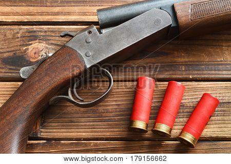 Shotgun and shells on wood. Top down view.