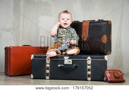 Retro photo. The child sits on a suitcase and with a camera in his hands