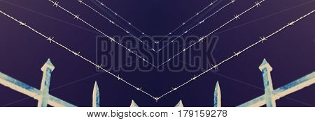 Night view of prison fence in barbed wire fence closeup - security escape concept