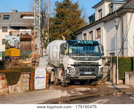 STRASBOURG FRANCE - MAR 13 2017: Powerful Volvo FMX truck with Liebherr cement mixer instalation working at the construction site on a tiny French street