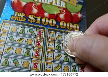 Coquitlam BC Canada - November 20, 2016 : Man scratching lottery ticket. The British Columbia Lottery Corporation has provided government sanctioned lottery games in British Columbia since 1985.