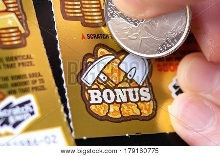 Coquitlam BC Canada - February 26, 2017 : Woman scratching lottery ticket on bonus section. The BC Lottery Corporation has provided government sanctioned lottery games in British Columbia since 1985.