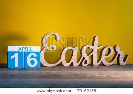Easter 2017 - April 16th. Calendar and carved of wooden text Easter at yellow background. Holiday concept.
