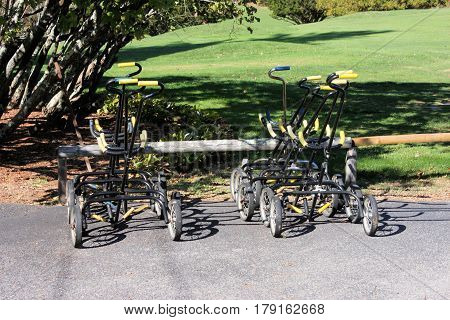 Group of two wheel hand carts at a golf course on a sunny day.