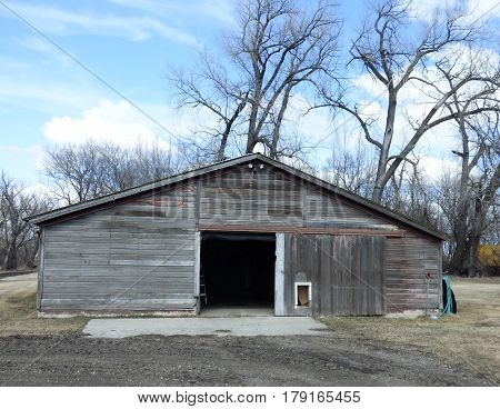 A old unpainted garage or storage building with a sliding door.