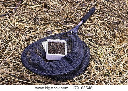 Anglers black fishing net and fresh box of works lying on muddy straw grass ground closeup