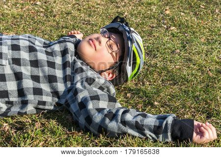 Boy youth lying on the grass basking in the sun with his bicycle helmet still on resting outdoor activities concept