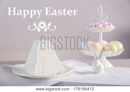 Plate with traditional curd cake on table. Text HAPPY EASTER on background