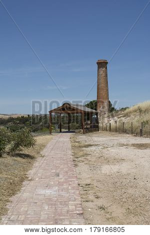Kapunda South Australia Australia - December 3 2016: Old historic chimney built in 1850 at the Kapunda Copper Mine. Also featuring the newer shelter and paved path that leads to it. Portrait orientation.